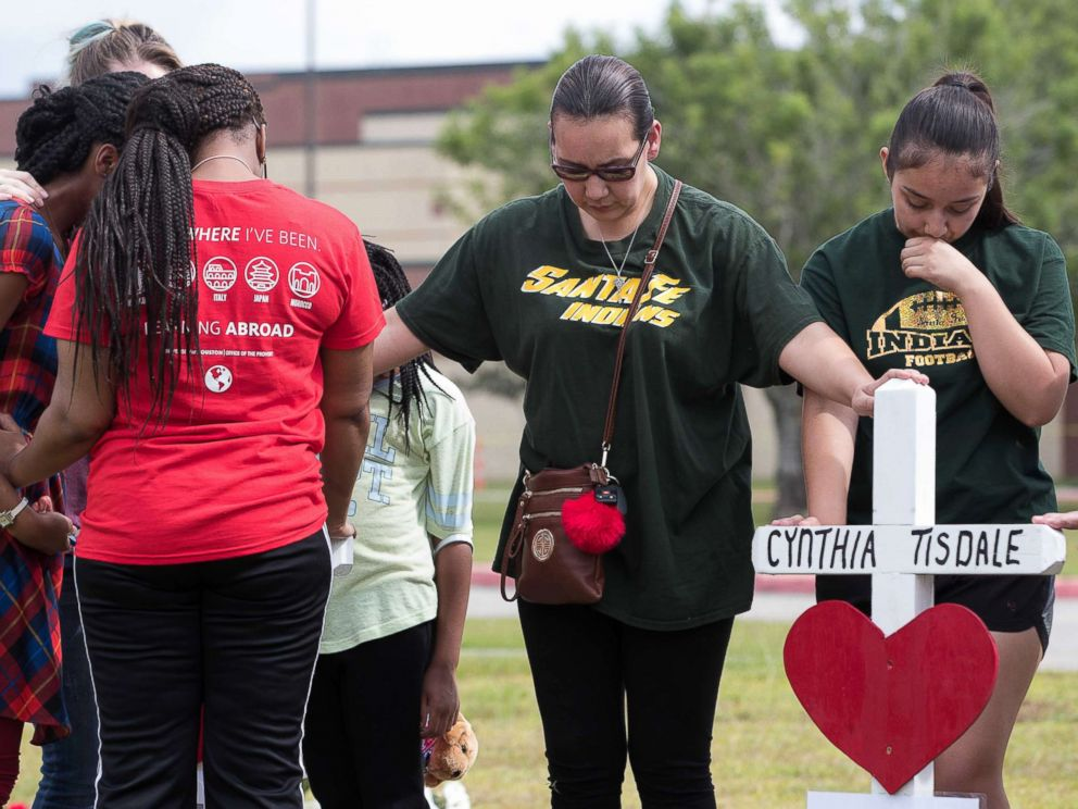 PHOTO: People place their hands on the crosses at the makeshift memorial outside Santa Fe High School during a moment of silence at 10am, May 21, 2018, in Santa Fe, Texas.