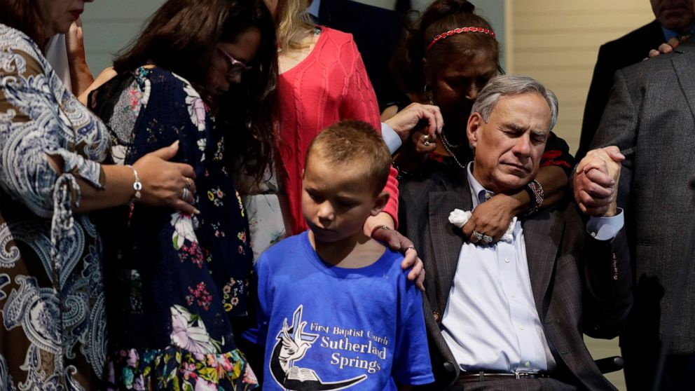 PHOTO: Texas Gov. Greg Abbott, right, holds hands with survivors during a dedication ceremony for a new sanctuary and memorial room at the First Baptist Church in Sutherland Springs, Texas, Sunday, May 19, 2019.