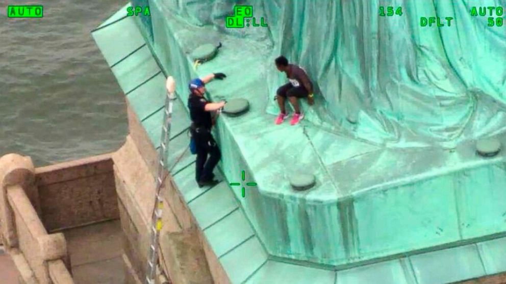 In an image made from video provided by the New York City Police Department, members of the NYPD Emergency Service Unit work to safely remove Therese Okoumou, who climbed onto the Statue of Liberty to protest the border separation of children, July 4, 2018.