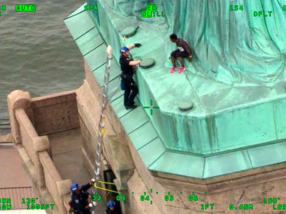 PHOTO: In an image made from video provided by the New York City Police Department, members of the NYPD Emergency Service Unit work to safely remove Therese Okoumou from the base of the Statue of Liberty, July 4, 201