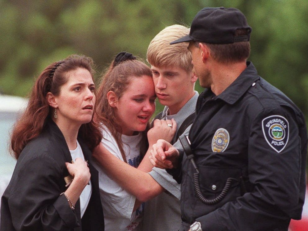 PHOTO: Students hug as a police officer walks past outside of Thurston High School in Springfield, Ore., May 21, 1998, after a student opened fire with a semiautomatic rifle in the high school cafeteria.