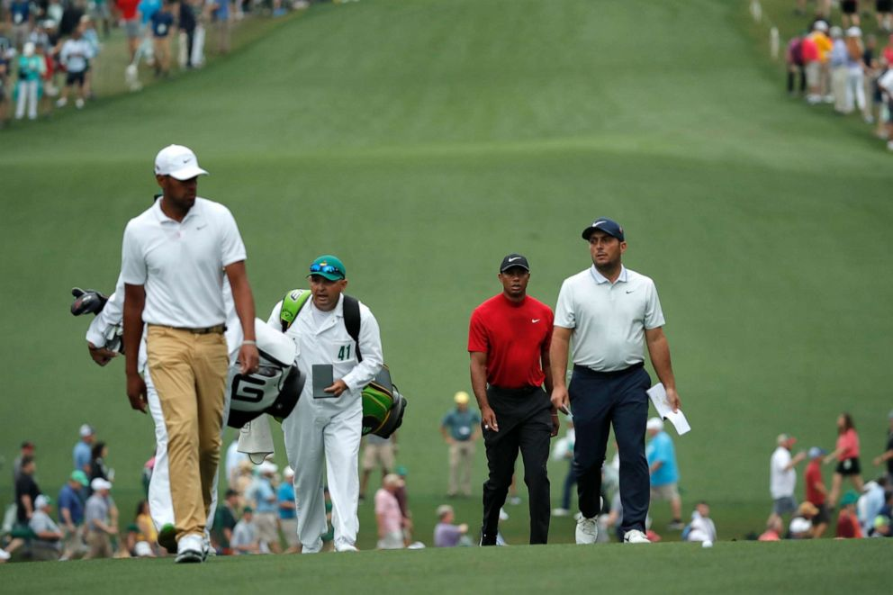 PHOTO: Francesco Molinari, Tiger Woods and Tony Finau walk up the first fairway during final round play at the Masters in Augusta, Ga., April 14, 2019.