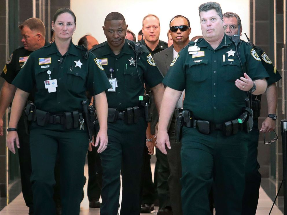 PHOTO: Tiger Woods, center right, makes his way into a North County Courthouse courtroom in Palm Beach Gardens, Fla., Oct. 27, 2017.