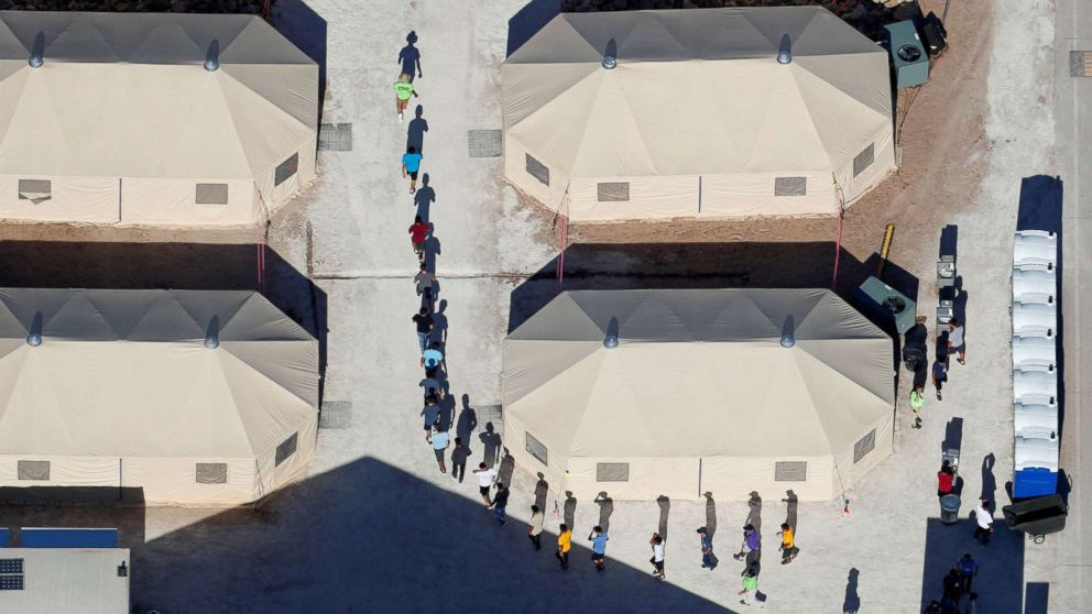 "Immigrant children, many of whom have been separated from their parents under a new ""zero tolerance"" policy by the Trump administration, walk in a single file between tents in their compound next to the Mexican border in Tornillo, Texas, June 18, 2018."