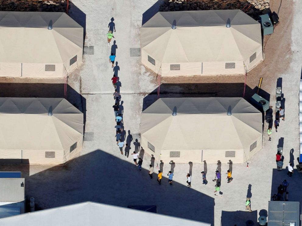 PHOTO: Immigrant children, many of whom have been separated from their parents, walk in a single file between tents in their compound next to the Mexican border in Tornillo, Texas, June 18, 2018.