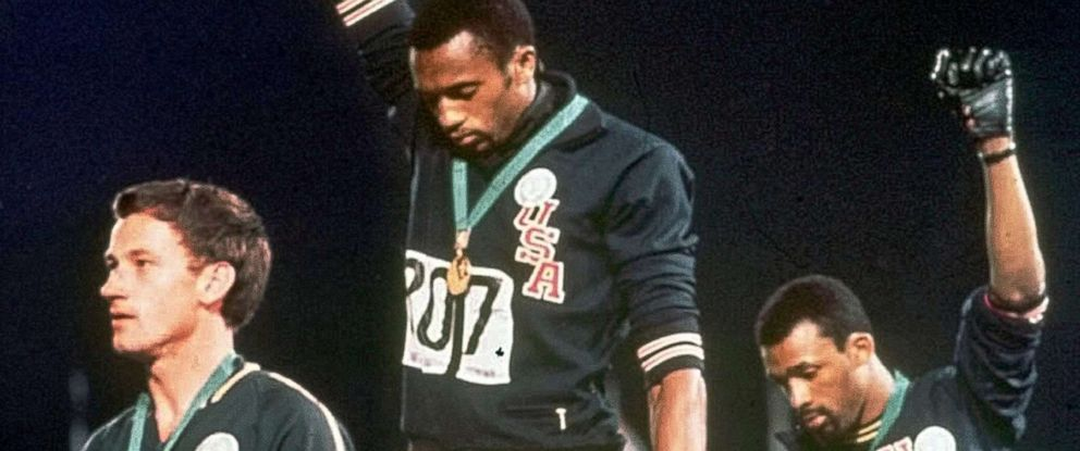 "PHOTO: Athletes Tommie Smith, center, and John Carlos stare downward during the playing of ""The Star-Spangled Banner"" after Smith received the gold and Carlos the bronze medal in the 200 meter run at the Summer Olympic Games in Mexico City."