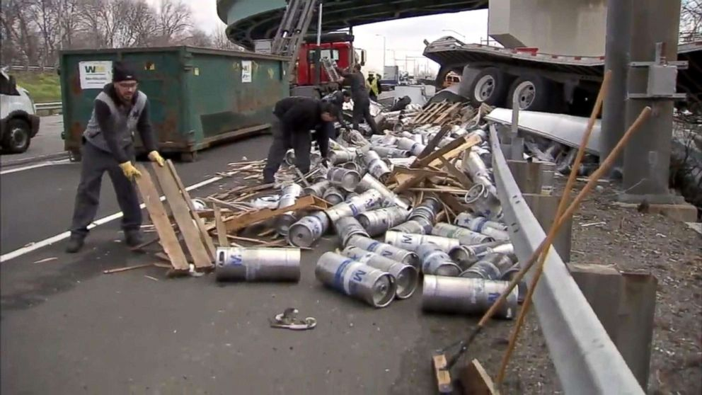 PHOTO: Crews work to remove hundreds of empty beer kegs and containers littered I-95 on Bensalem, Bucks County, PA, April 10, 2018, after a trucked plunged more than 20 ft.
