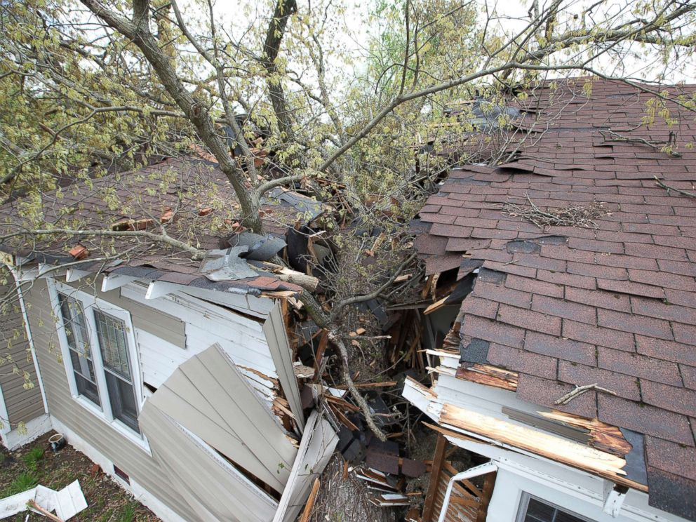 PHOTO: A tree cleaves the house on Oak Grove Avenue the day after a tornado hit, killing one person and leaving devastation throughout eastern portion of the city, April 16, 2018, in Greensboro, N.C.