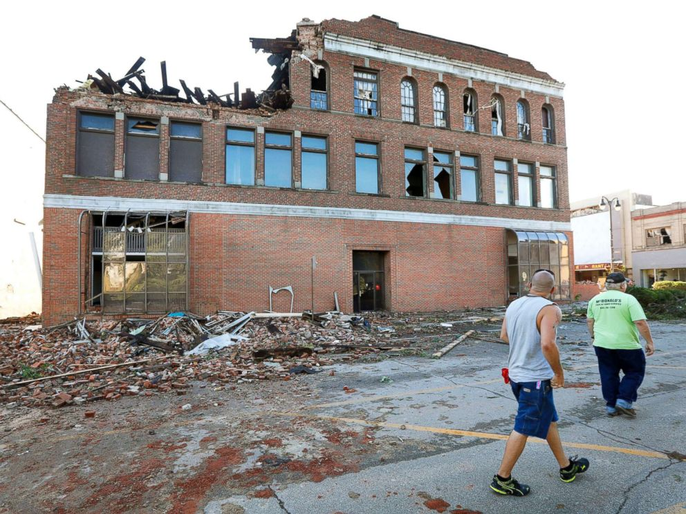 PHOTO: Local residents walk past a tornado-damaged building on Main Street, July 19, 2018, in Marshalltown, Iowa.