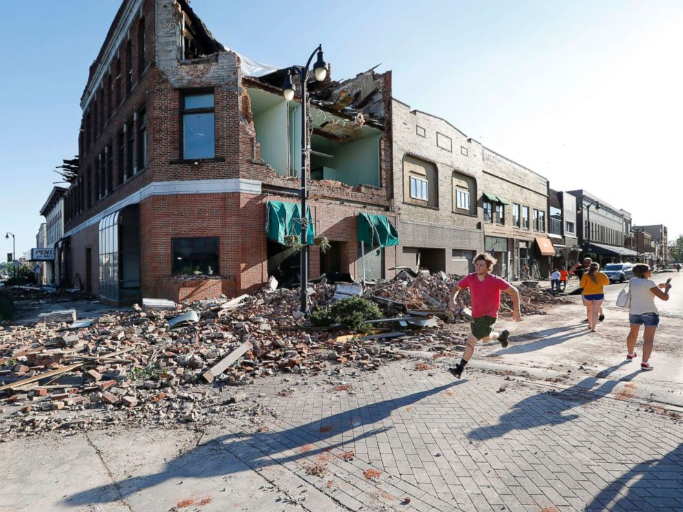 PHOTO: A local resident runs past a tornado-damaged building on Main Street, July 19, 2018, in Marshalltown, Iowa.