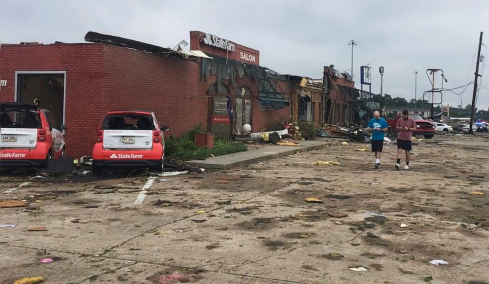PHOTO: A pair of men walk though the parking lot of a strip mall that was destroyed by a deadly tornado that tore through the northern Louisiana city of Ruston early Thursday, April 25, 2019.