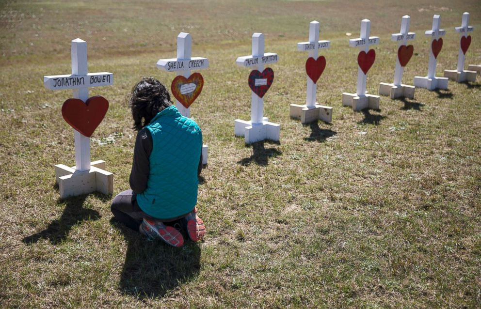 Jessica Taylor prays in front of a cross for Jonathan Bowen, 9, at a makeshift memorial for the victims of a tornado in Beauregard, Ala., March 6, 2019.