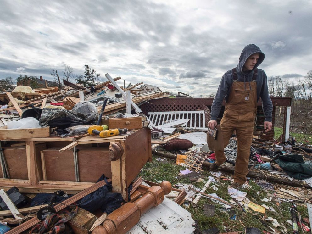 PHOTO: Ryan Polaski sorts through debris of his father-in-laws house after severe weather, April 16, 2018 in Elon, Va.