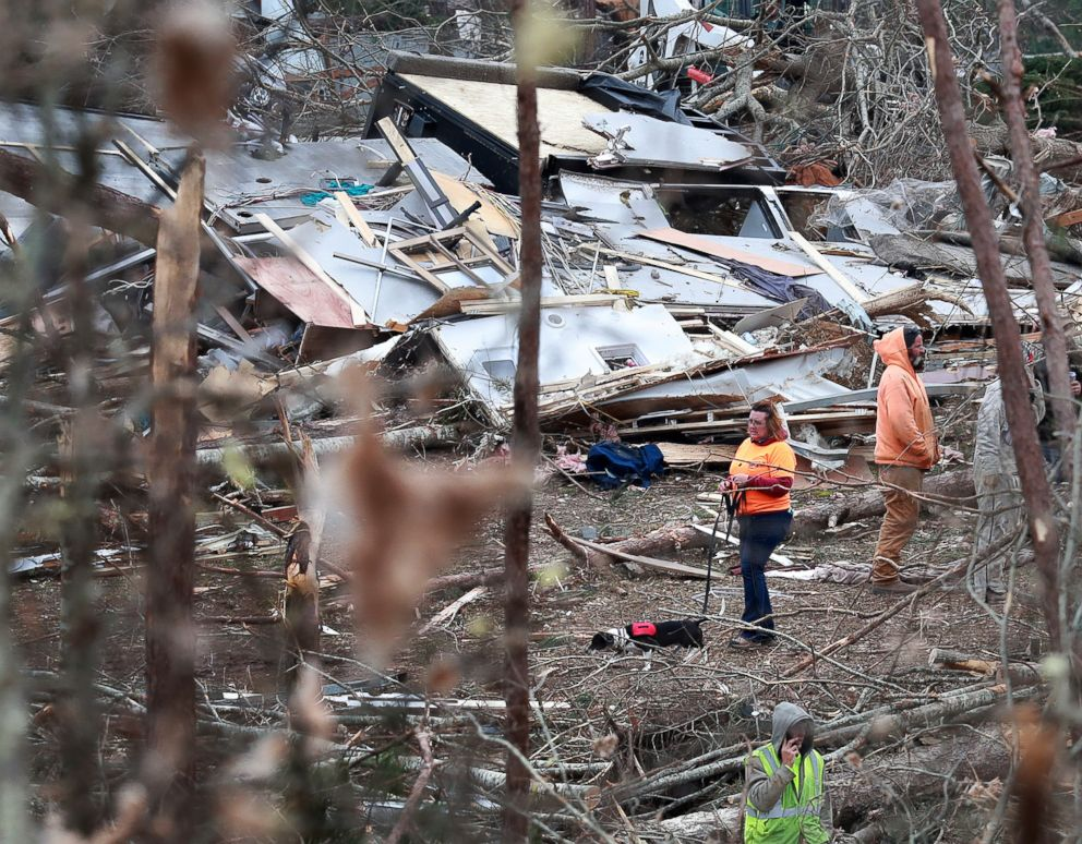 PHOTO: A woman and her dog make their way through the wreckage of shattered homes, March 4, 2019, as rescue workers, residents and volunteers sift through the debris following a tornado, in Beauregard, Ala.