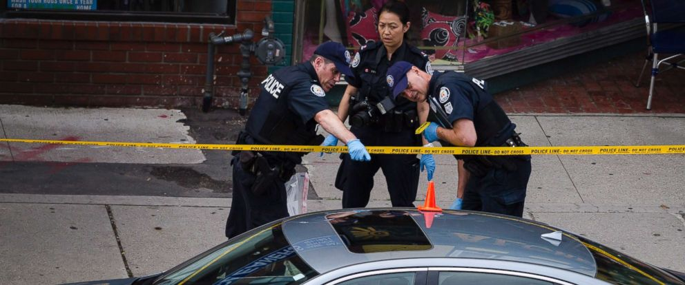 PHOTO: Police investigate a car with a bullet hole within the scene of a shooting in east Toronto, on July 23, 2018.