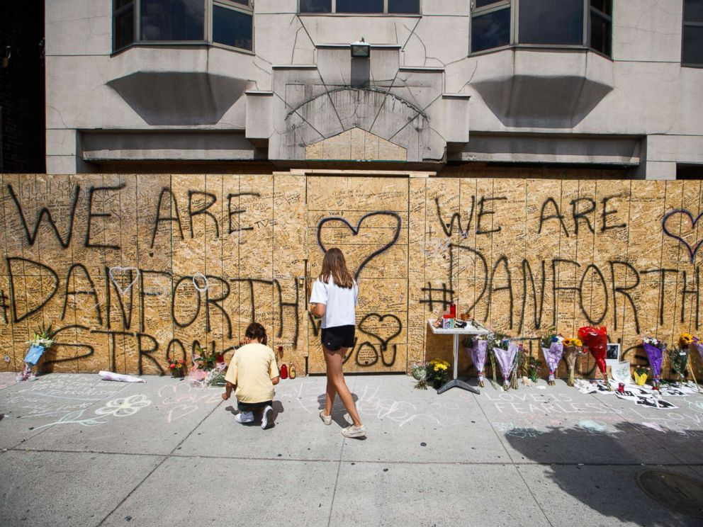 PHOTO: People write messages on a makeshift memorial, July 24, 2018, in Toronto, for the victims of Sundays shooting.