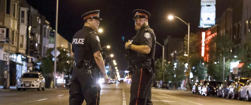 PHOTO: Toronto police officers stand watch at the foot of Danforth St. at the scene of a shooting in Toronto, July 23, 2018. A gunman opened fire in central Toronto on Sunday night, injuring 13 people including a child.
