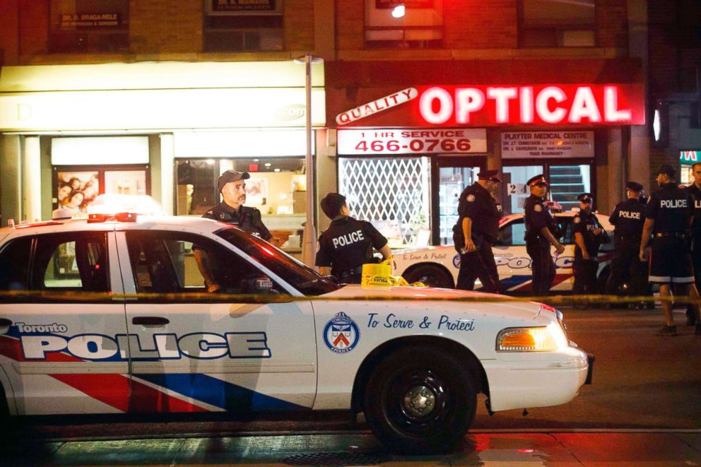PHOTO: Toronto Police officers walk the scene at Danforth St. at the scene of a shooting in Toronto, July 23, 2018.