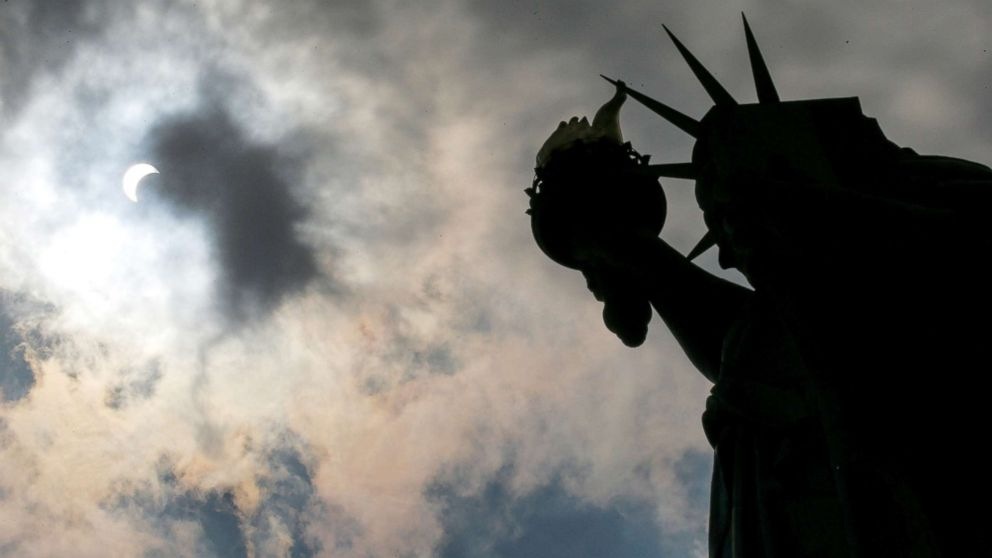 The Monument of Liberty State is photographed while the solar eclipse is seen over Liberty State Island in New York, Aug. 21, 2017.