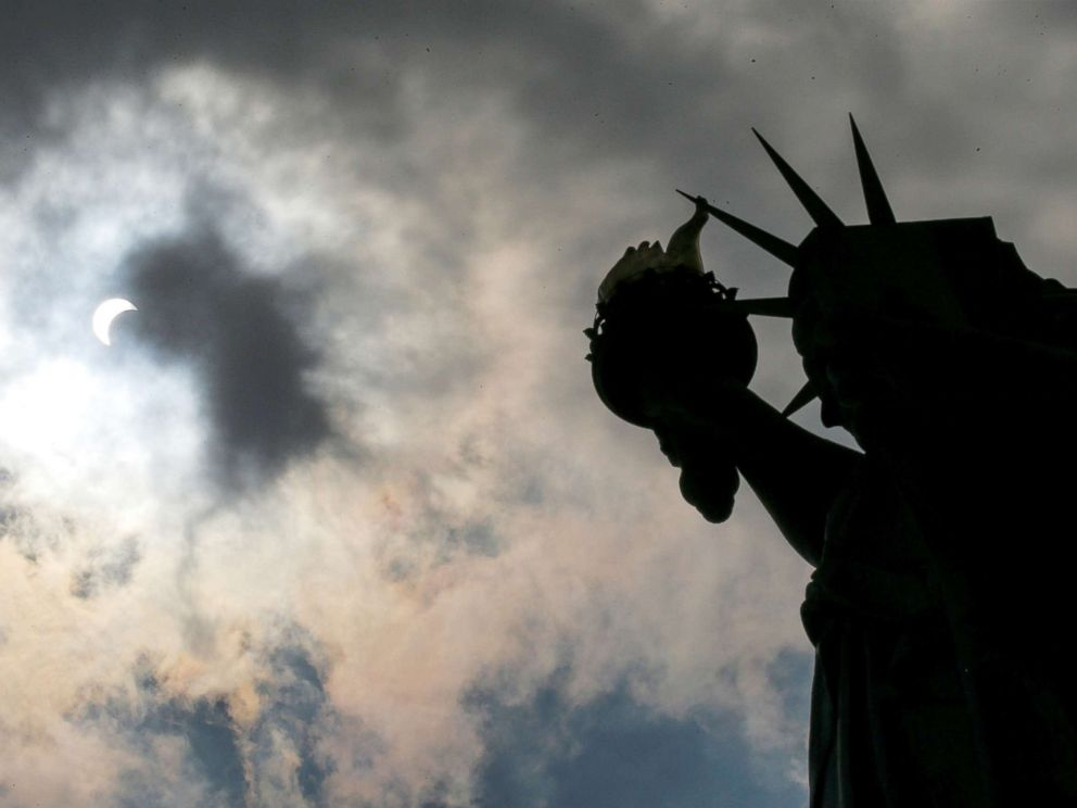 PHOTO: The Monument of Liberty State is photographed while the solar eclipse is seen over Liberty State Island in New York, Aug. 21, 2017.