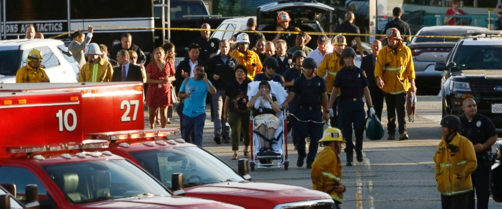 Los Angeles officials escort a woman being evacuated by emergency personnel after a gunman held hostages inside a Trader Joes store in Los Angeles, July 21, 2018.