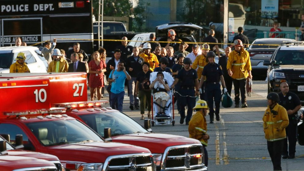 Los Angeles officials escort a woman being evacuated by emergency personnel after a gunman held hostages inside a Trader Joe's store in Los Angeles Saturday, July 21, 2018.