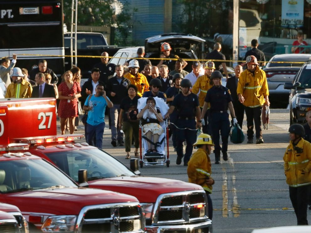 Los Angeles officials escort a woman being evacuated by emergency personnel after a gunman held hostages inside a Trader Joes store in Los Angeles Saturday, July 21, 2018.