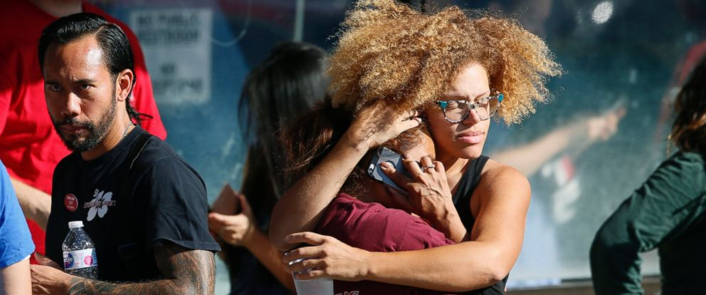 Unidentified Trader Joes supermarket employees hug after being evacuated by Los Angeles Police after a gunman barricaded himself inside the store in Los Angeles Saturday, July 21, 2018.