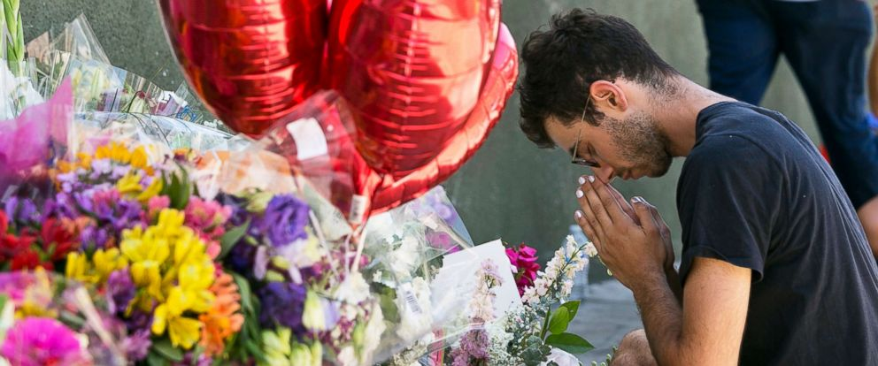 PHOTO: Paolo Singer, 27, a Silver Lake resident, prays at a makeshift memorial of flowers, candles and notes growing on the sidewalk outside the Silver Lake Trader Joes store in Los Angeles, July 23, 2018.