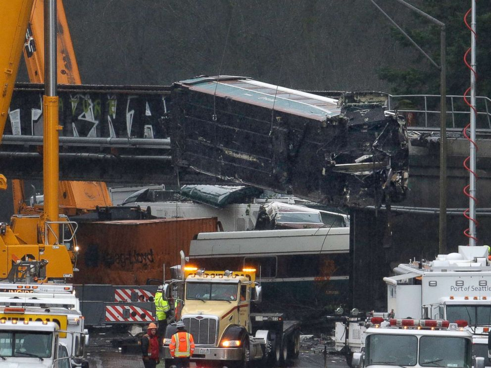 PHOTO: A damaged Amtrak train car is lowered from an overpass at the scene of Mondays deadly train crash onto Interstate 5, Dec. 19, 2017, in DuPont, Wash.