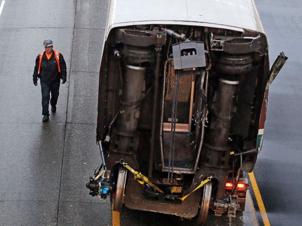 PHOTO: A worker walks along a damaged train car atop a flat bed trailer taken from the scene of Mondays deadly Amtrak train crash onto Interstate 5, Dec. 19, 2017, in DuPont, Wash.