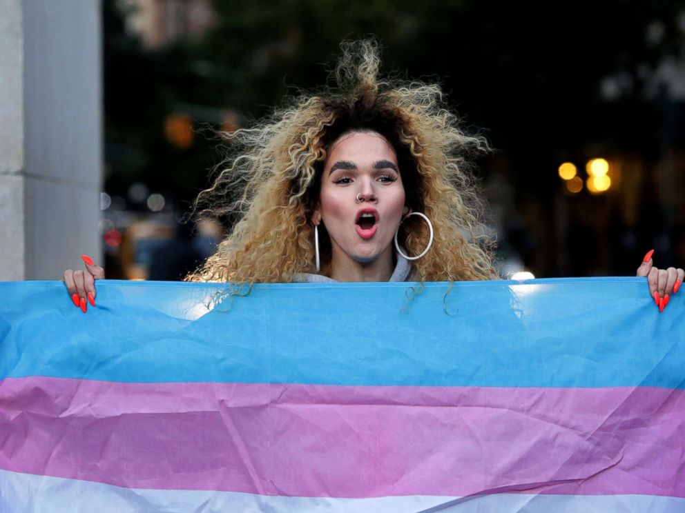 PHOTO: Morgin Dupont, 25, a woman of trans experience, holds up the flag for Transgender and Gender Noncomforming people at a rally for LGBTQI+ rights at Washington Square Park on October 21, 2018 in New York City.