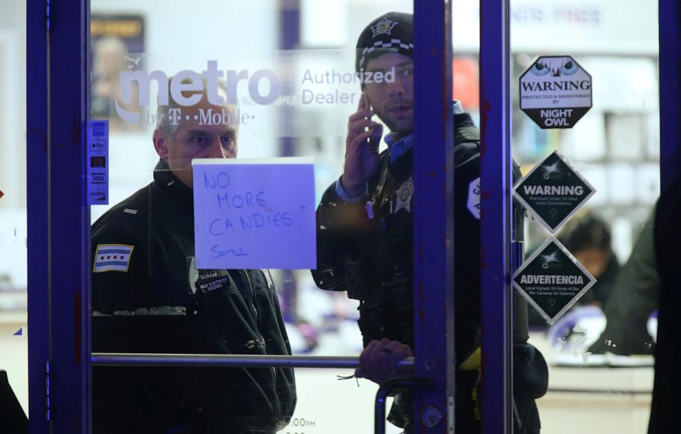 PHOTO: A police supervisor and officer stand inside a cellphone store in the 3700 block of West 26th Street in Chicago, where a 7-year-old girl who was shot while trick-or-treating was brought inside until transported, on Thursday, Oct. 31, 2019.