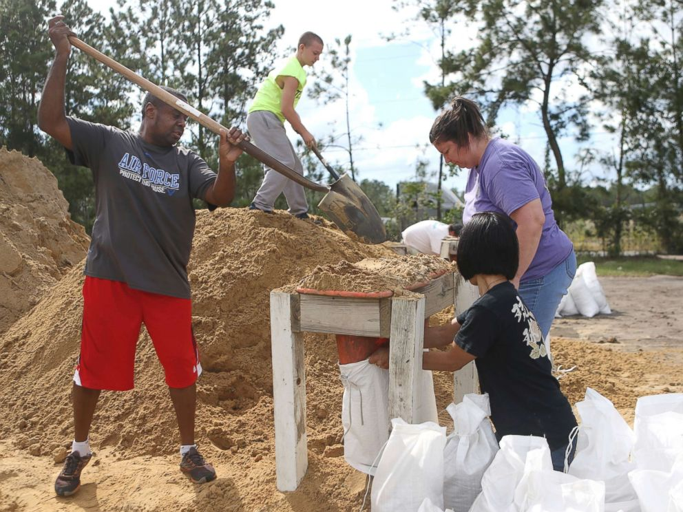 PHOTO: From left, Haskel Johnson, Daniel Tippett, Jennifer Tippett and Nobuko Johnson fill sand bags at the Lynn Haven Sports Complex in Lynn Haven, Fla., Oct. 8, 2018, to prepare for Hurricane Michael.