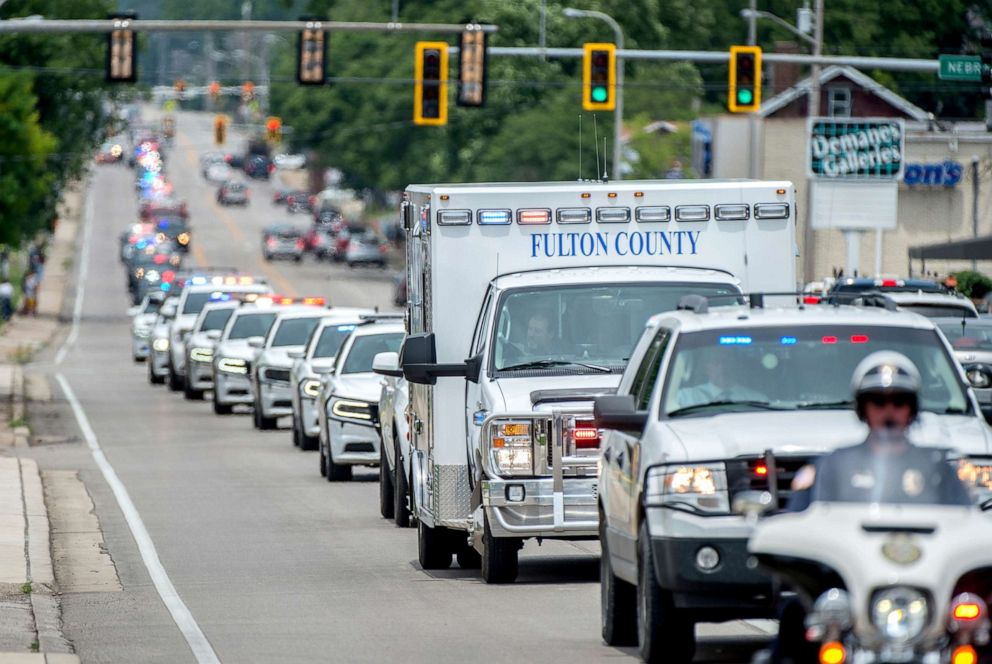 PHOTO: A long line of emergency vehicles, including an ambulance carrying the remains of Fulton County Sheriffs Deputy Troy Chisum, heads to a Lewistown funeral home on June 26, 2019 in Peoria.