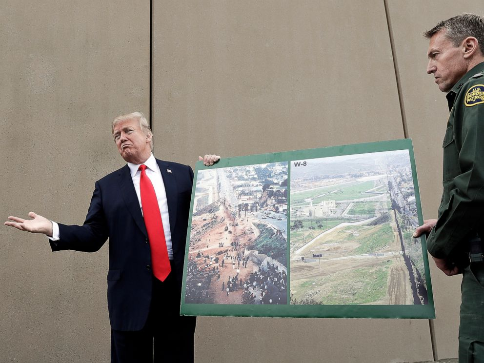 PHOTO: In this March 13, 2018, file photo, President Donald Trump holds a poster with photographs of the U.S.-Mexico border area as he reviews border wall prototypes in San Diego with Rodney Scott, the U.S. Border Patrols San Diego sector chief.