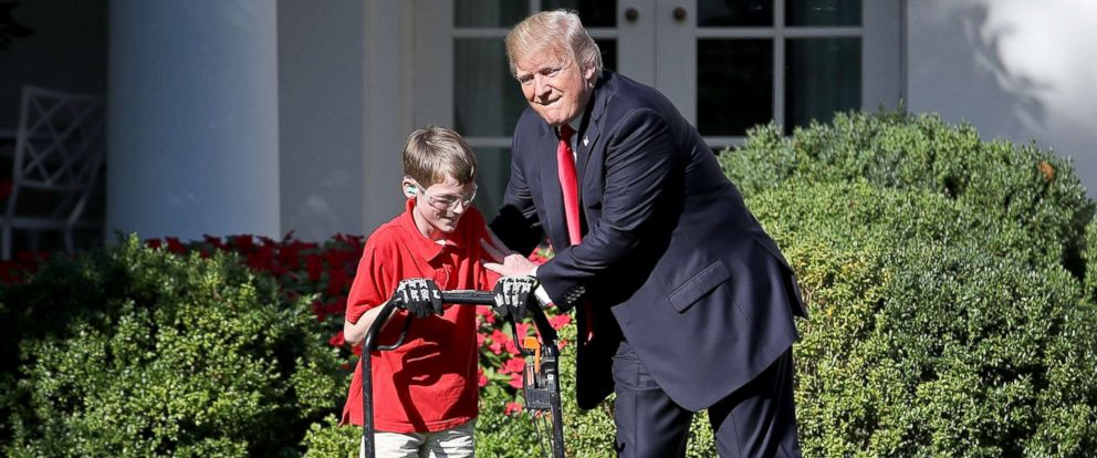 "PHOTO: Frank ""FX"" Giaccio, 11, gets a pat on the back from President Donald Trump while mowing the grass in the Rose Garden of the White House, Sept. 15, 2017, in Washington."