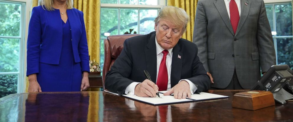 PHOTO: Watched by Homeland Security Secretary Kirstjen Nielsen (L) and Vice President Mike Pence, President Donald Trump signs an executive order on immigration in the Oval Office of the White House on June 20, 2018.