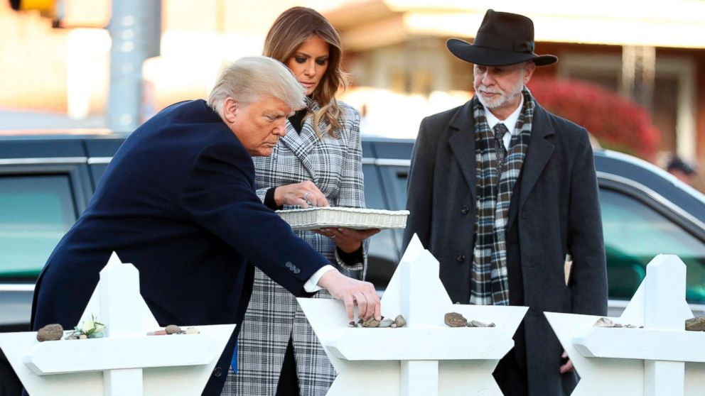 President Donald Trump and first lady Melania Trump put down stones from the White House at a memorial outside for those killed at the Pittsburgh's Tree of Life Synagogue in Pittsburgh, Oct. 30, 2018, as Tree of Life Rabbi Jeffrey Myers watches.