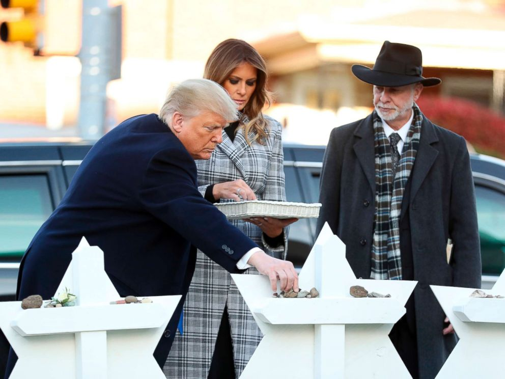 PHOTO: President Donald Trump and first lady Melania Trump put down stones from the White House at a memorial outside for those killed at the Pittsburghs Tree of Life Synagogue in Pittsburgh, Oct. 30, 2018, as Tree of Life Rabbi Jeffrey Myers watches.