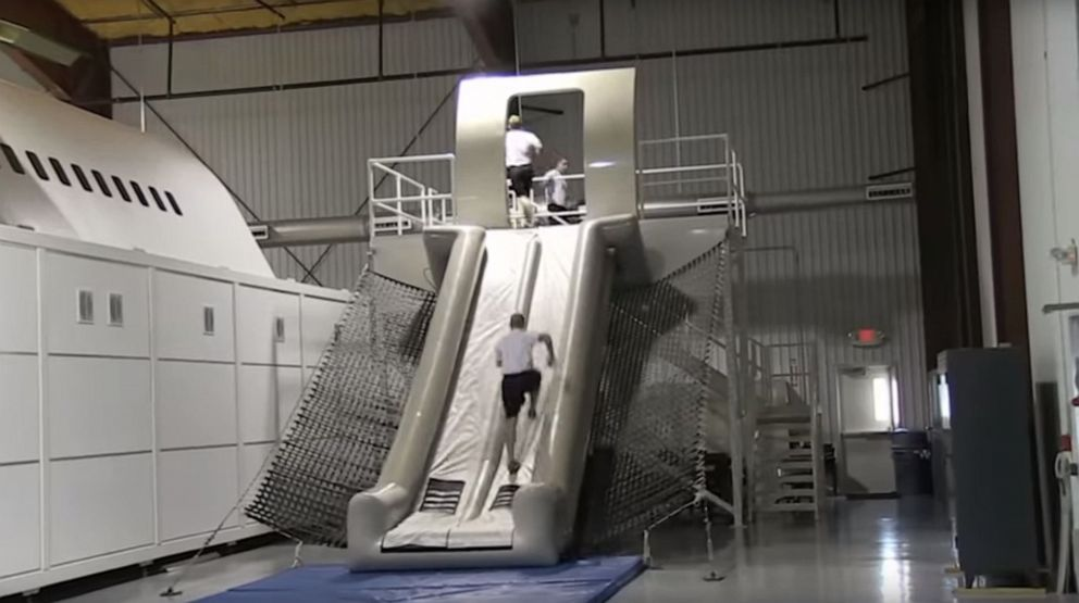 PHOTO: A Federal Air Marshal Service trainee runs up an inflatable evacuation slide.