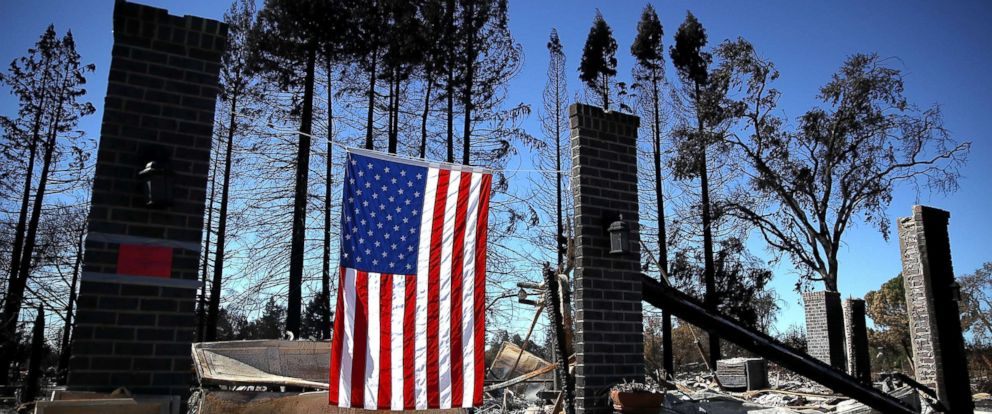 PHOTO: An American flag hangs in front of a home in the Coffey Park neighborhood that was destroyed by the Tubbs Fire, Oct. 23, 2017, in Santa Rosa, Calif.