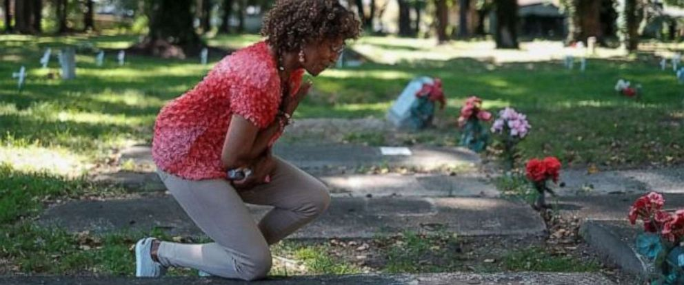 PHOTO: Brenda Tucker, a descendent of one of the first black Americans William Tucker whose parents were brought from Angola on the first ship carrying enslaved Africans to Virginia in 1619, pays her respects at a family members grave.