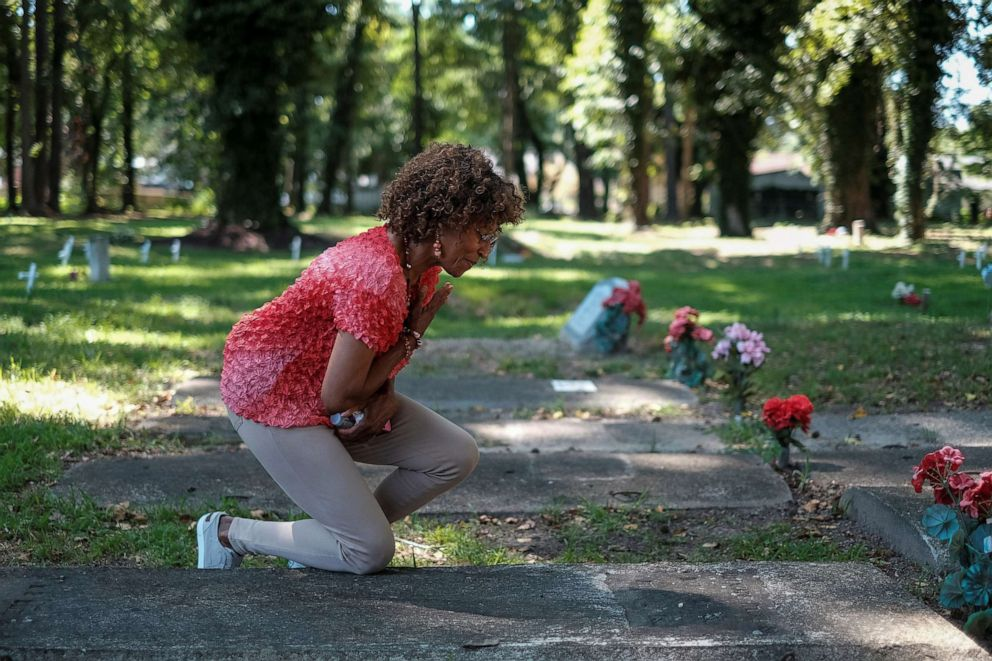 PHOTO: Brenda Tucker, a descendent of one of the first black Americans William Tucker, pays her respects at a family members grave at the Tucker family cemetery in Hampton, Virginia, July 27, 2019.