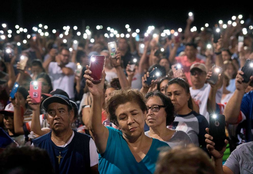 PHOTO: People hold up their phones during a prayer and candlelight vigil organized by the city of El Paso, after a shooting left 20 people dead at the Cielo Vista Mall Wal-Mart, Aug. 4, 2019.