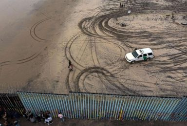 PHOTO: An aerial view of migrants who form part of the Central American migrant caravan being detained and escorted by a border patrol agent after crossing the US-Mexico border fence in Playas de Tijuana, Baja California state, Mexico, Dec. 9, 2018.