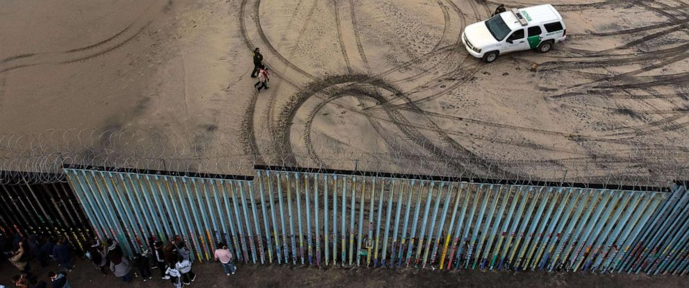 PHOTO: An aerial view of migrants who form part of the Central American migrant caravan being detained and escorted by a border patrol agent after crossing the U.S.-Mexico border fence in Playas de Tijuana, Baja California state, Mexico, Dec. 9, 2018.