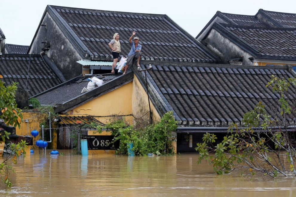 PHOTO: People stand on the roof of their house along a submerged street in the UNESCO heritage ancient town of Hoi An after typhoon Damrey hit Vietnam, Nov. 6, 2017.