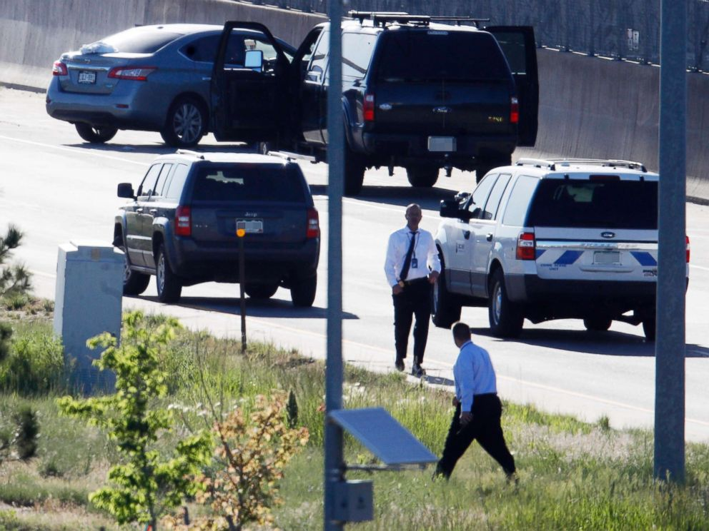 PHOTO: Denver Police Department detectives, investigate near where a Nissan sedan, top left, being driven by an Uber driver crashed into a retaining wall along Interstate 25 south of downtown Denver, June 1, 2018.