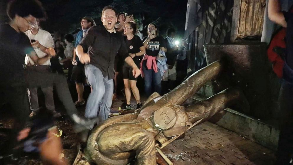 """Protesters celebrate after the Confederate statue known as """"Silent Sam"""" was toppled on the campus of the University of North Carolina in Chapel Hill, N.C., Aug. 20, 2018."""